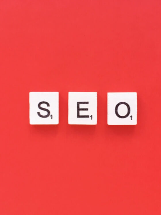 Image of the letters SEO spelled out with scrabble pieces on a red background.