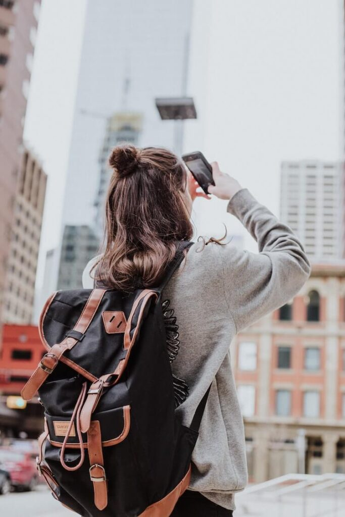 Image of a girl with a backpack, taking a photo of a city Skyscraper.