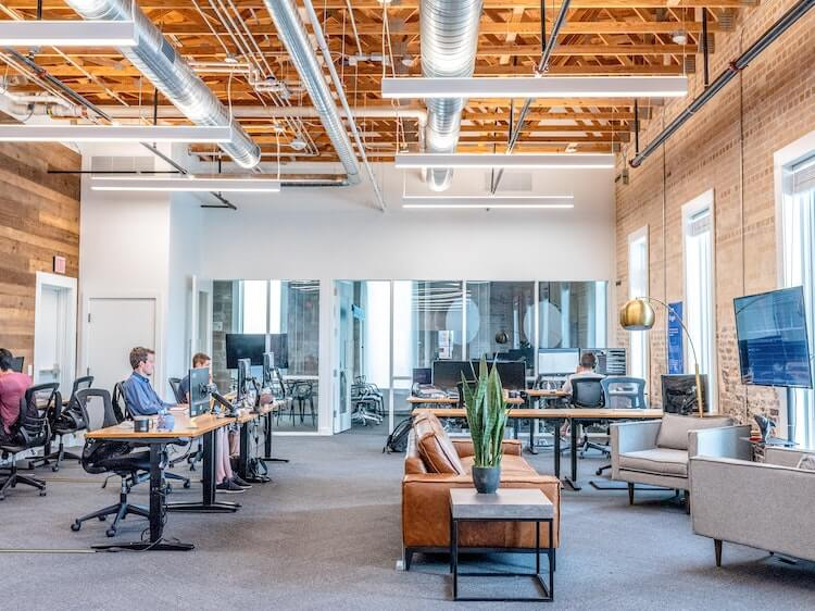 Open office workspace with sofas and tables.