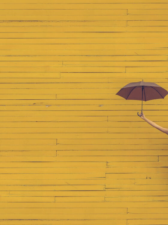 Woman jumping with umbrella in front of yellow wall.