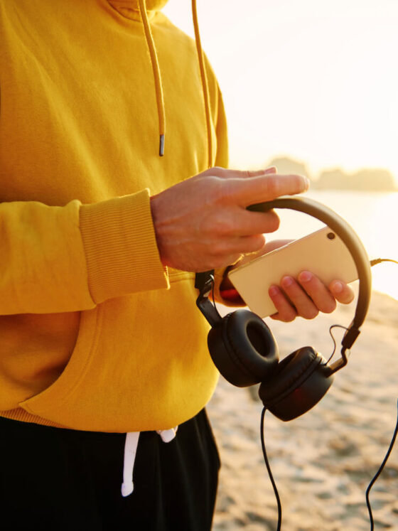 Man running along the beach in the morning, stopped to put on a playlist of songs.