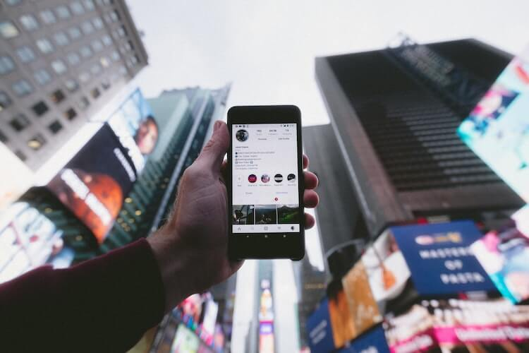 Phone open to an Instagram Profile against city background.