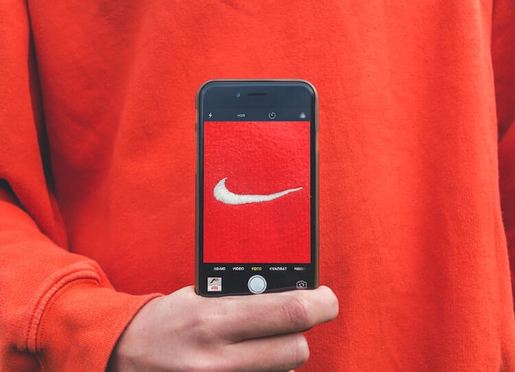 Phone camera displaying the recognizable nike logo in front of a red sweatshirt.
